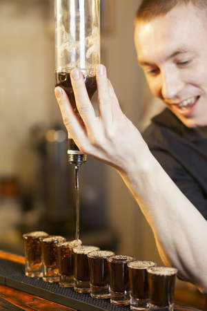bartender fills a few glasses in a row at the same time photo