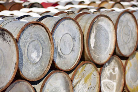 Old oil barrels stacked piles at the dump