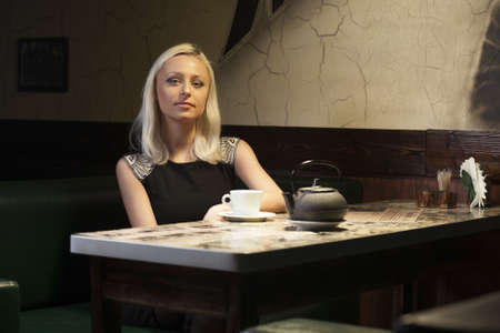pretty woman in cafe sitting alone have a cup of tea