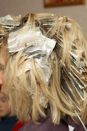 woman in hair salon with coloring foil on her head Stock Photo