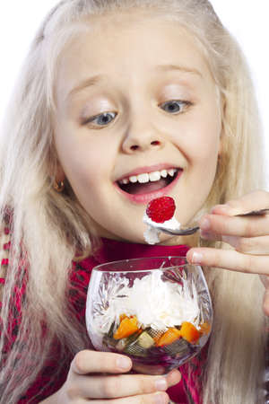 Happy beautiful girl eating dessert with fruits photo