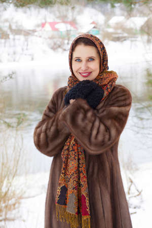Beautiful russian woman in fur coat and shawl standing on coast photo