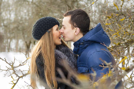 Young guy trying to kiss girl in winter park photo