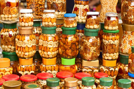 sweetmeats: glass jars with nuts and honey on counter in a market as the background