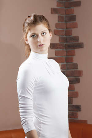 Earnest woman in white shirt standing against a wall Stock Photo - 18419853