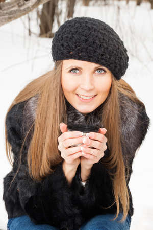 Portrait of dark blond young woman with hot drink in winter photo