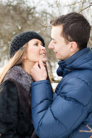 Happy Young Couple in Winter garden kissing. photo