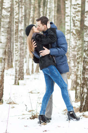birchwood: Happy Young Couple in Winter birchwood kissing Stock Photo