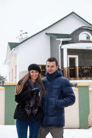 Young beautiful couple standing embracing near his new house photo