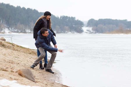 Couple playing on the coast of winter river Stock Photo - 18484874