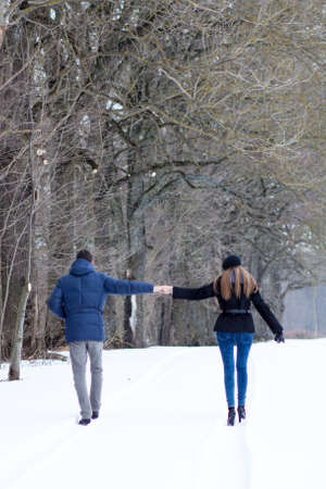 Couple walking in winter park happy and joyful
