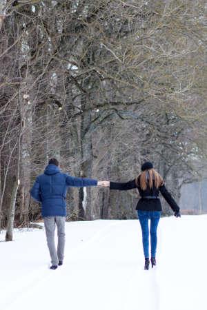 Couple walking in winter park happy and joyful