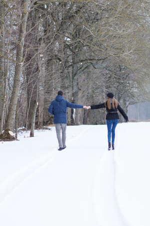 Couple walking in winter park happy and joyful photo