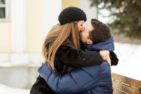 young couple hugging kissing: Lovers kissing on the bench in winter park