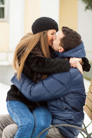 lovers kissing: Lovers kissing on the bench in winter park