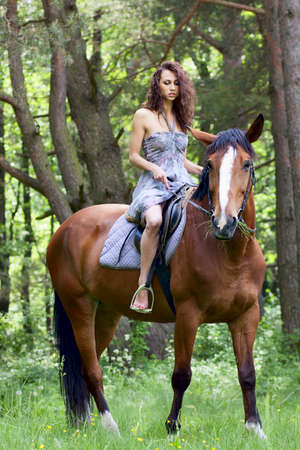 east riding: beautiful young girl on horse in dress in forest