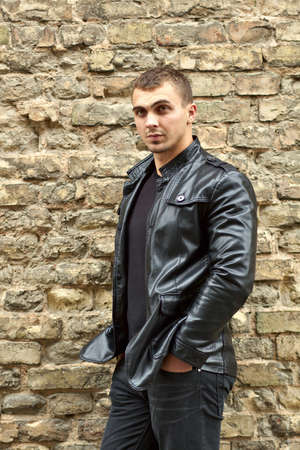 Closeup portrait of the brutal young sexual man in a leather jacket photo