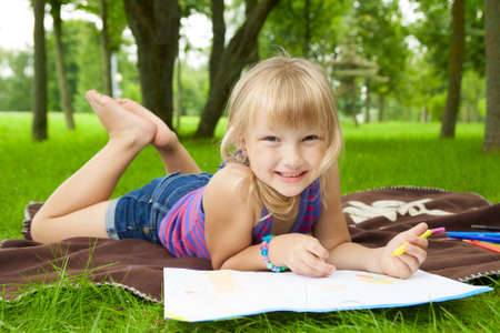 little girl drawing in the park on the grass photo