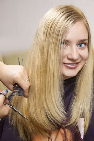 hairdressing scissors: Hairdresser giving a new haircut to female