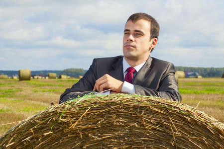 A business man in a suit is based on the stack of hay photo