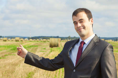 Business man in a suit pointing at copy space photo