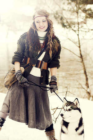 Happy young woman standing with siberian husky dog in winter forest photo