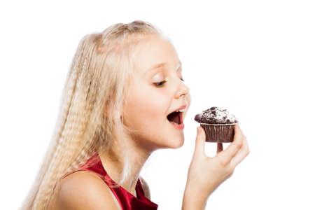 Girl biting a chocolate cake. Isolated on white background. photo