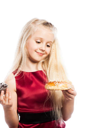 Girl making a choice between two cakes. Isolated on white background. photo