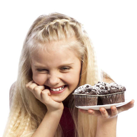 Girl looking at chocolate muffins. Isolated on white background. photo