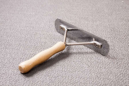 De-shedding tool from metal with wooden handle photo