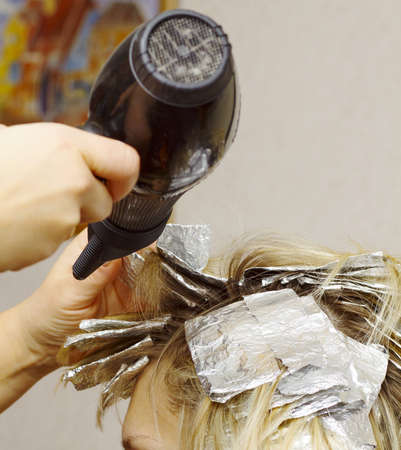 woman with coloring foil on her hair in salon photo