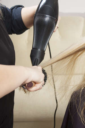 Hairdressers hands drying long blond hair with blow dryer and round brush photo