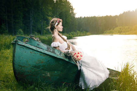 Beautiful young bride sitting on boat on the lake photo