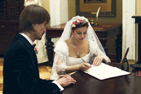 The bride and groom sign the marriage contract in office photo