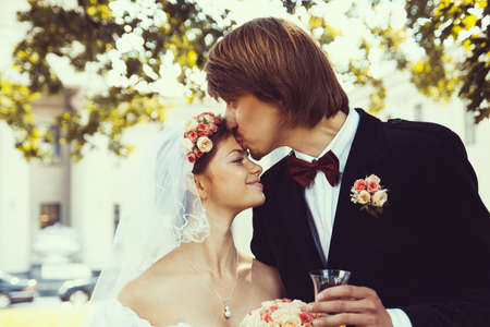 Beautiful groom kissing young bride in forehead photo