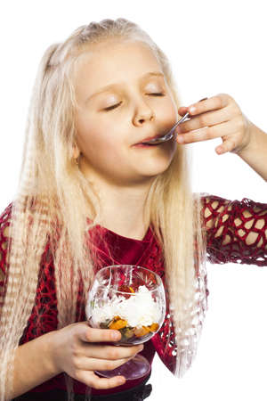 Beautiful blonde girl eating dessert isolated over white background photo
