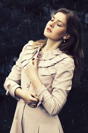 Beautiful sensual girl standing in the rain photo