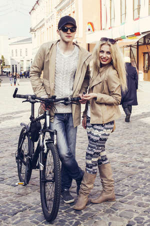Caucasian couple with bicycle standing on a street photo