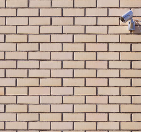 Surveillance digital camera on the brick wall photo