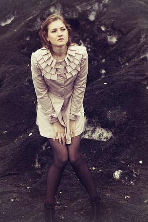 lovesickness: Beautiful sad girl standing on dirty ground Stock Photo