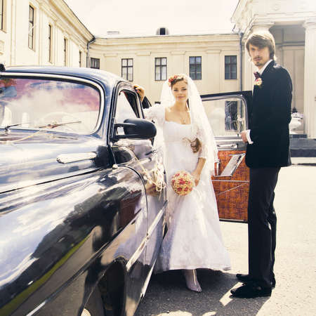 Beautiful happy young bride and groom standing near a retro auto photo