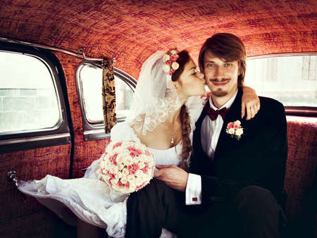 Beautiful happy young bride and groom kissing in retro auto photo