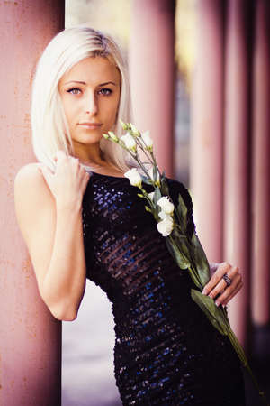 Beautiful blonde girl with white rose in hands photo