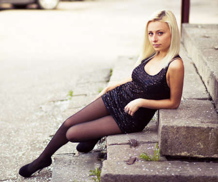 Girl is sitting on the stone steps