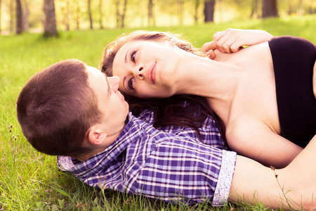 Young happy couple resting on the grass. photo