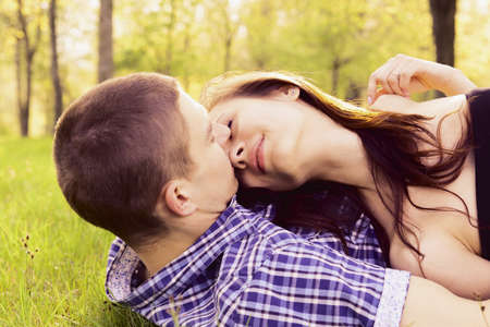 Young happy couple kissing on the grass. photo