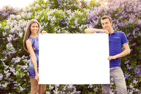 Young couple holding blank poster against the background of lilac bush photo