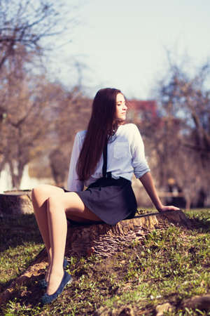 Beautiful girl sitting on a tree stump photo