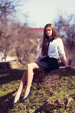 Beautiful girl sitting on a tree stump