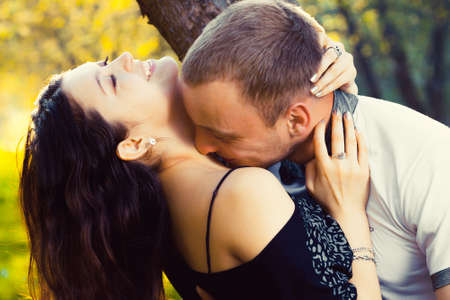 happy young couple kissing in the summer park photo
